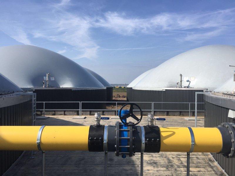 De vergisters met de op de voorgrond de gasleiding waardoor het biogas stroomt.